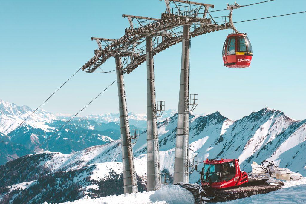 un chasse neige rouge qui passe sous un téléphérique rouge à la montagne en hiver