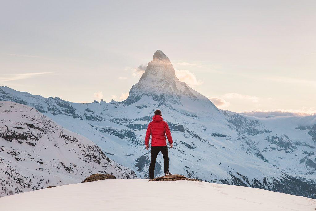 Un homme de so face à une montagne enneigée
