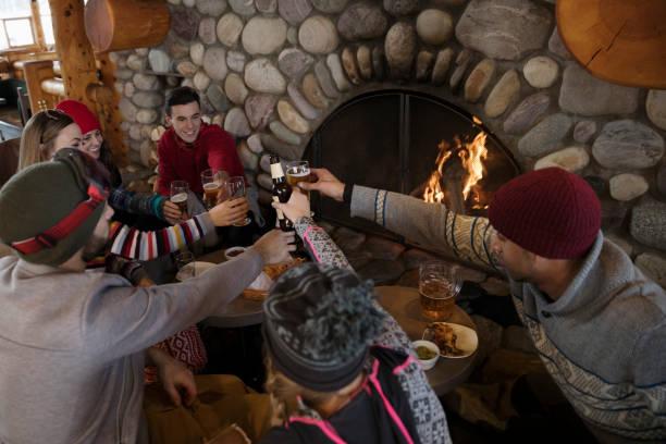 Groupe d'amis en train de boire et manger près d'une cheminée dans un chalet de montagne
