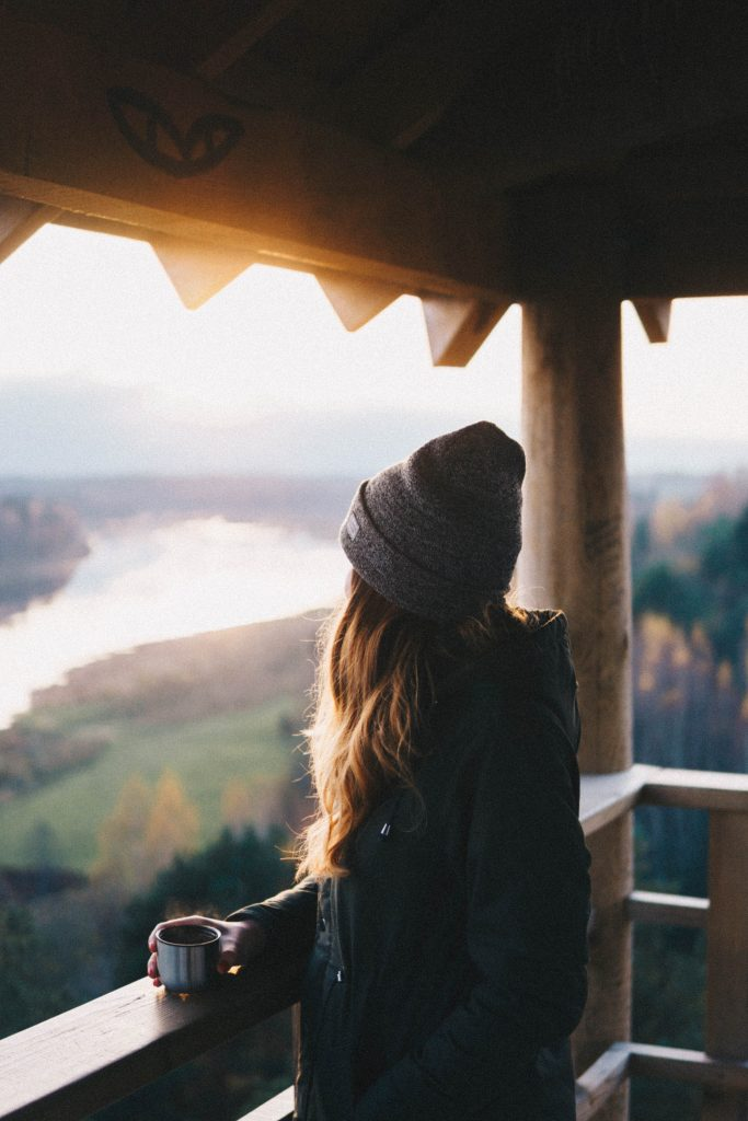Jeune femme déjeunant face à la vue sur les montagnes depuis un balcon de chalet en bois