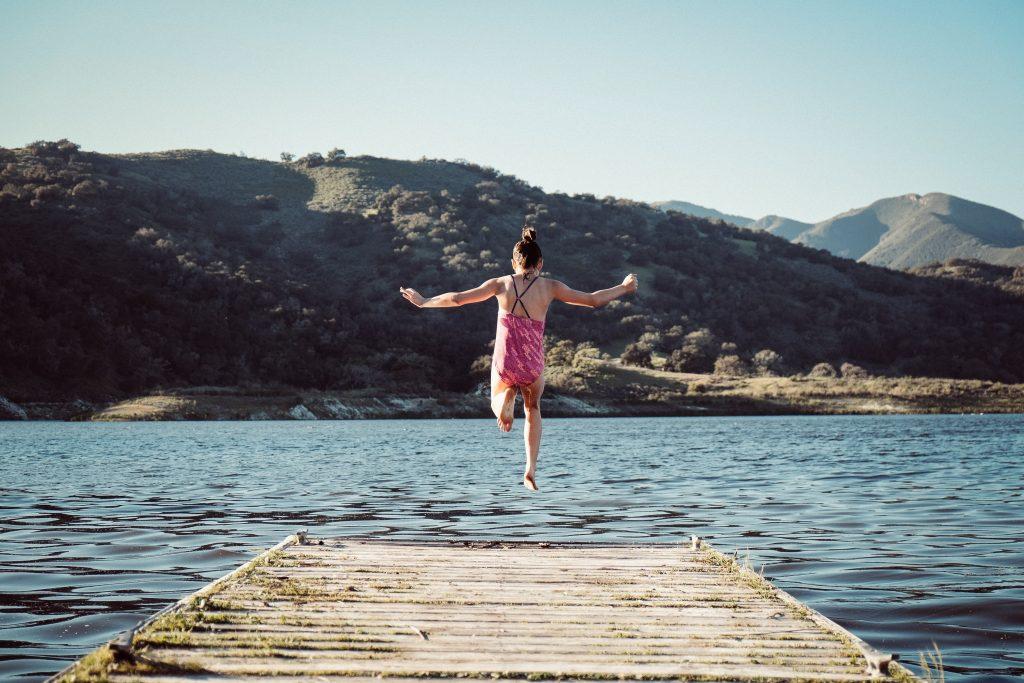Petite fille qui saute dans l'eau, dans un lac de montagne