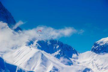 Montagne enneigée avec un parapente en premier plan