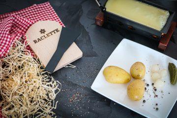 raclette avec assiette de pommes de terre et poêlon de fromage fondu