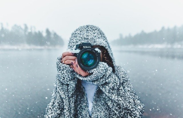photo avec fond de neige et une personne avec une appareil photo de face
